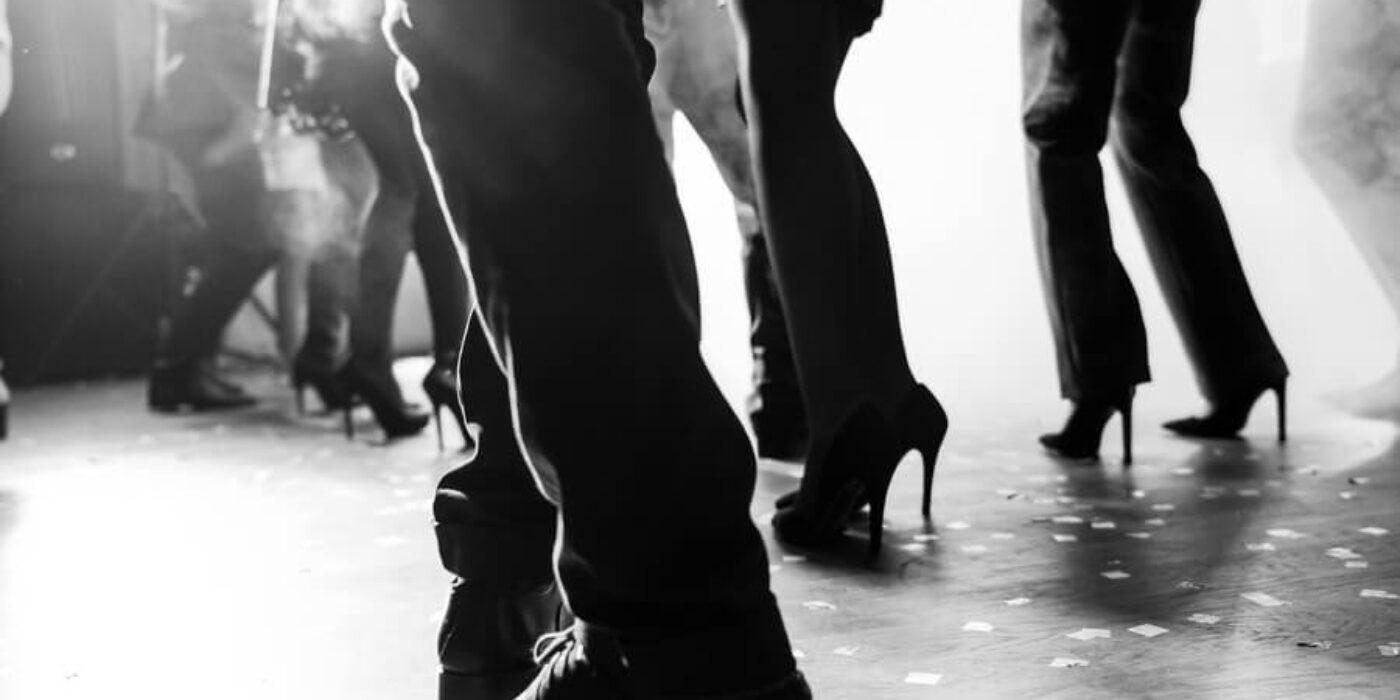 guests dancing on wooden dance floor bw